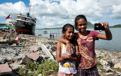 Mary Ann, 10, and Mary Grace, 14, take a selfie front of Anibong Bay in Tacloban, Philippines. Photo: Eleanor Farmer/Oxfam
