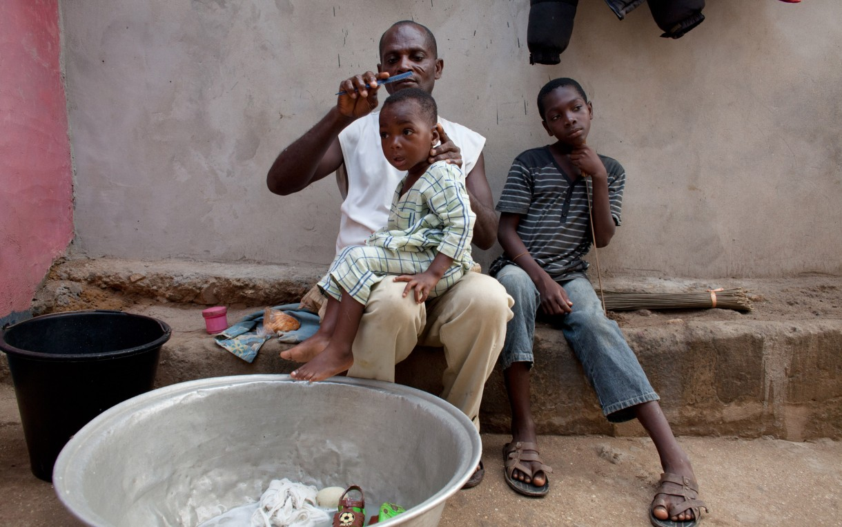 Steven Arthur finishes bathing and dressing his youngest son outside his home in Abuesi, Ghana. On days when Arthur is not at sea fishing, he takes charge of these household chores before he goes to work in the morning. Photo: Jane Hahn/Oxfam America