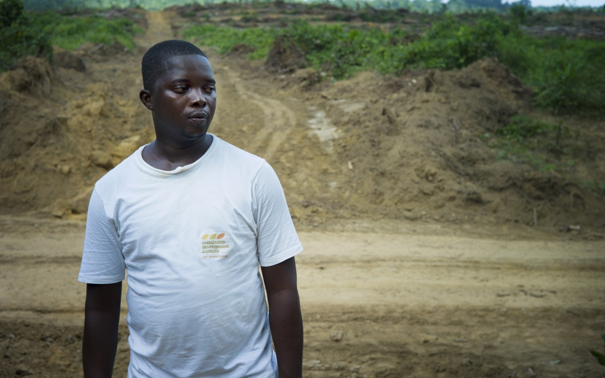 """Daniel Krakue, who works for Social Entrepreneurs for Sustainable Development in Liberia, in a recently cleared part of the Butaw oil palm concession: """"Nowadays we don't have a specific month as to when the rain will start and when it will end. So that has caused serious problems as to how people will carry on their farming."""" Photo by Anna Fawcus/Oxfam America."""