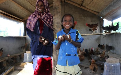 Mariam Maussa and her daughter, Aisha, collect eggs from some of the chickens being raised by women who have formed a co-op. Maussa is the leader of the co-op. Photo: Ella Dickinson/Oxfam