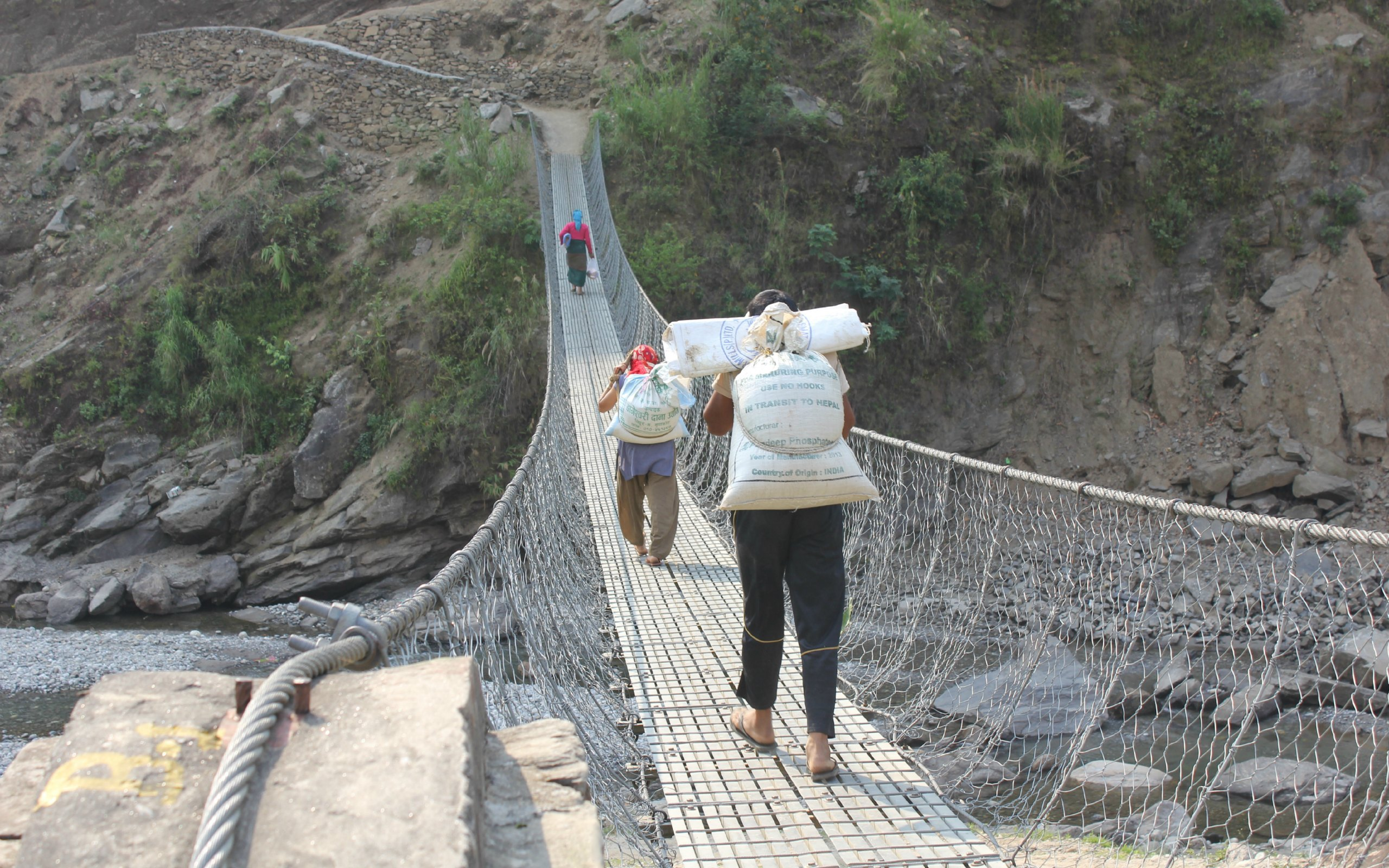 People affected by the earthquake in Nepal cross a suspension bridge carrying items from Oxfam's food distribution in Saatbise, Nuwakot. About 450 households affected by the earthquake received items on one day.