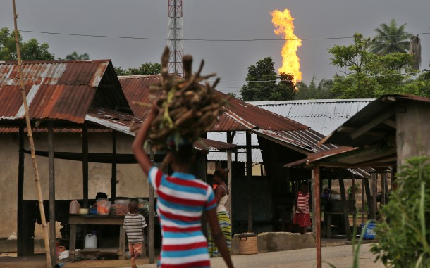 A gas flare looms over the community of Akaraolu, in the Niger Delta. Gas flares, with constant noise, ash, and noxious fumes are just one of the negative effects on oil-producing areas of Nigeria. Photo by George Osodi/Panos for Oxfam America