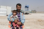 """Housam Shayeb and his son, from Ghouta, near Damascus in Syria, fled their home after the chemical attacks in 2014. Now Housam is part of Oxfam's """"cash for work"""" program at Zataari camp in Jordan, which is home to around 80,000 Syrian refugees. The program employs Housam to keep his district clean and to maintain Oxfam's facilities there. Photo: Sam Tarling/Oxfam"""