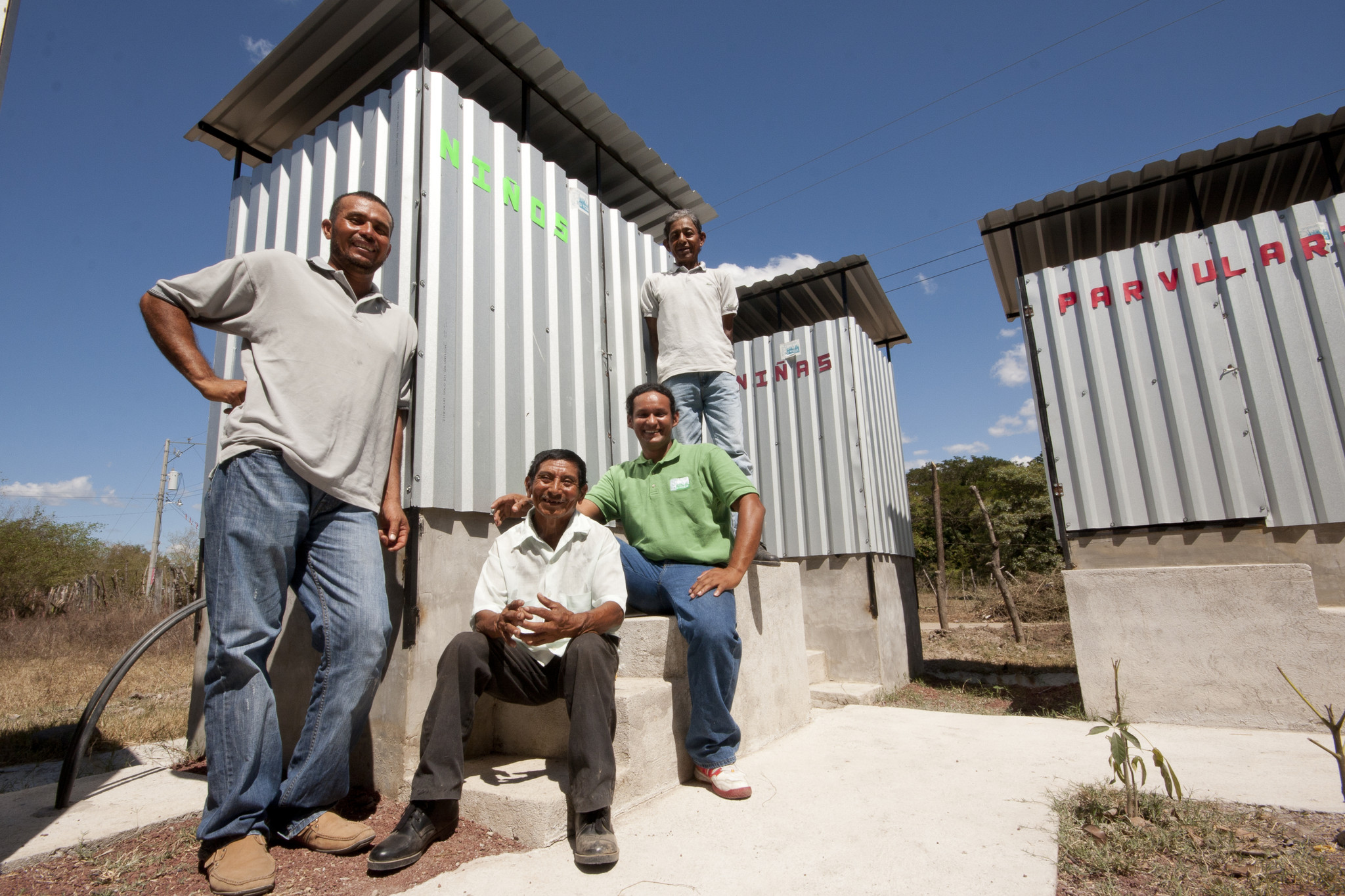 Members of a local public health team show visitors newly built composting latrines in El Salitral, El Salvador. Composting latrines are less likely to pollute nearby water sources in the event of heavy rains accompanying tropical storms, a recurring threat to the country. Photo: René Figueroa/Oxfam America Hernández, and José Eulalio Ortiz - members of the community of El Salitral - with Juan Ramon Flores (green shirt) - health promoter for Oxfam partner PROVIDA and a member of the national WASH team - pose with composting latrines installed at a school by PROVIDA.