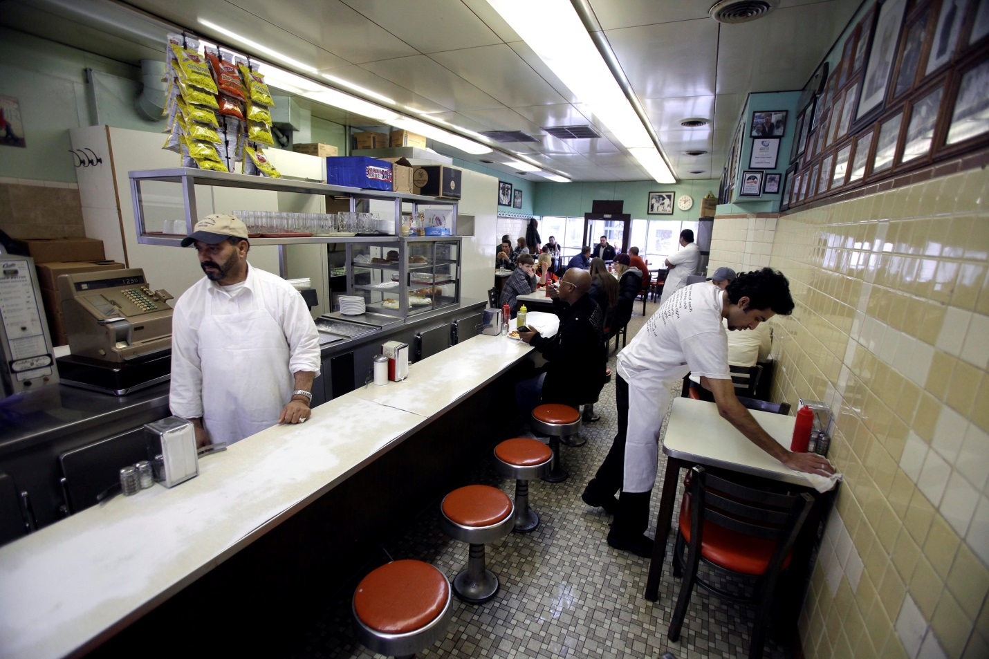 A waiter clears a table at Lafayette Coney Island restaurant in Detroit, Michigan, February 24, 2013. Photo: J.D. Pooley / Getty Images