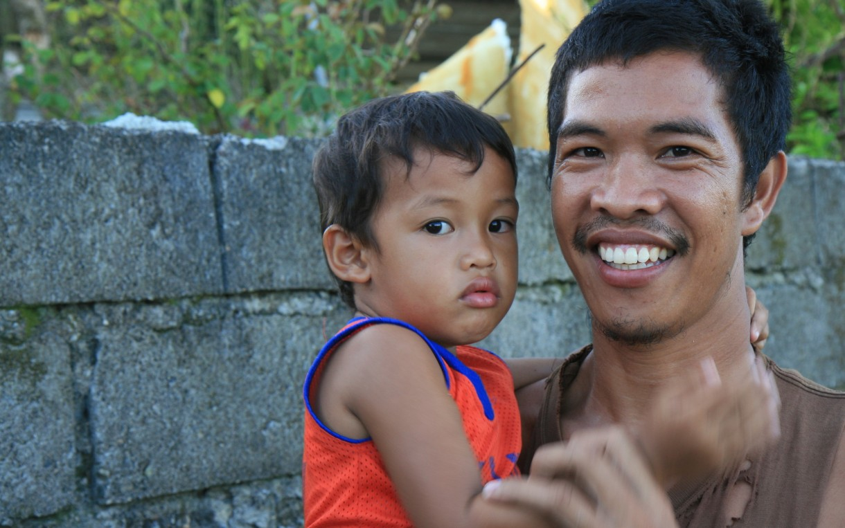 "Rice Farmer Gorgonio Simborio holds his son Viran, age 3 in Leyte, Philippines after Typhoon Haiyan/Yolanda. He says, ""Preparing our land for planting was delayed due to Yolanda coming and the money problems it caused us. At the moment we are relying on relief food. My wife is away in Manila working so we can get some kind of income. So for now I'm a single dad."" Photo: Jane Beesley / Oxfam"