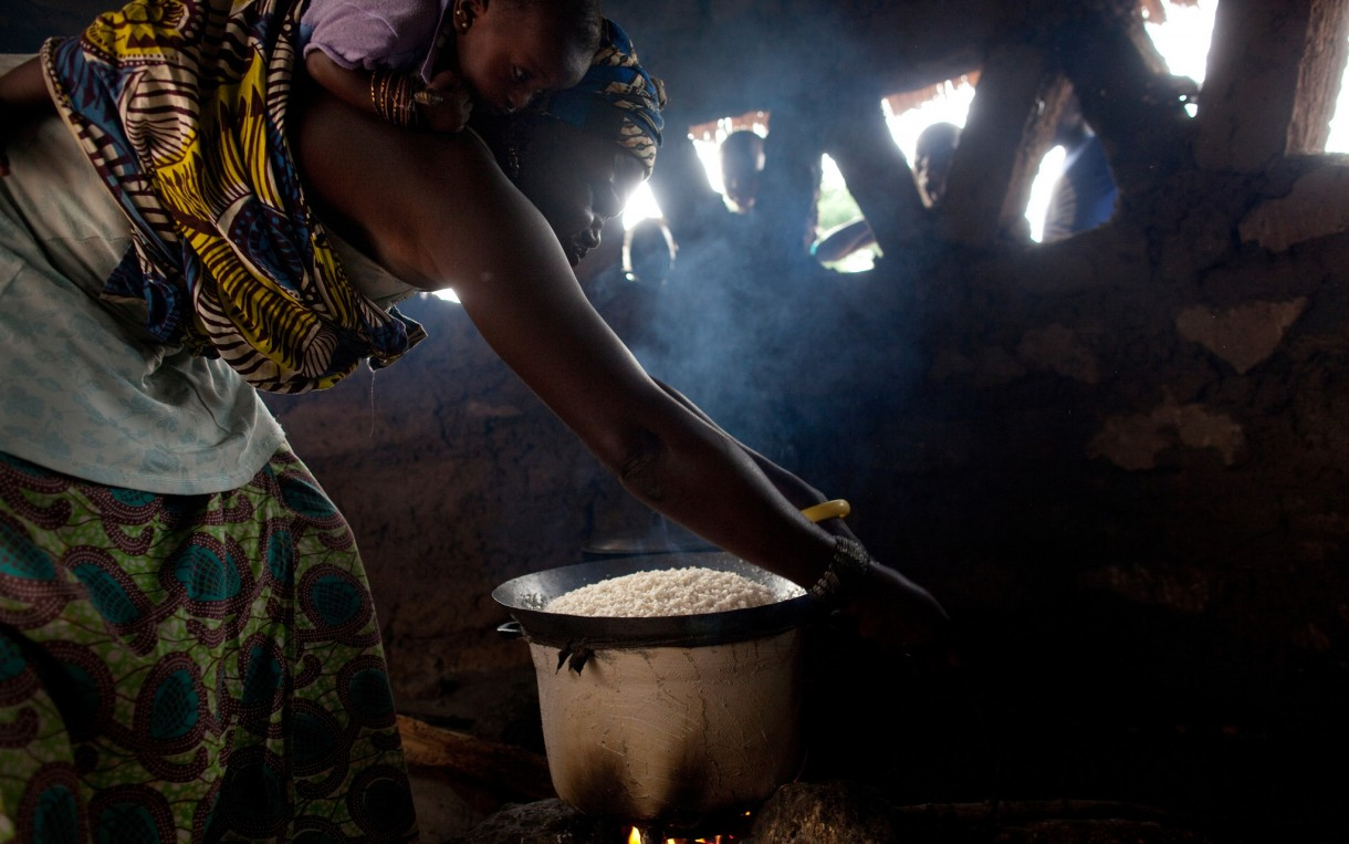 Karfa Mane begins to prepare rice for supper - with her granddaughter secured to her back - in the kitchen area of her home in Sare Dembara, Senegal. Photo: Holly Pickett / Oxfam America