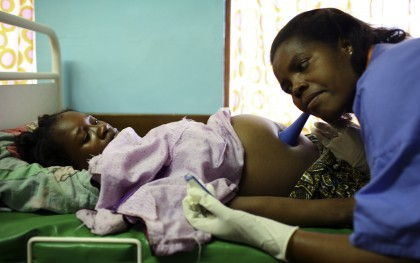 Nurse Melifa Mphasa listens to the pregnant belly of her patient in the labor ward at Bwalia 'Bottom' Hospital in Lilongwe, Malawi. Photo: Abbie Trayler-Smith / Oxfam