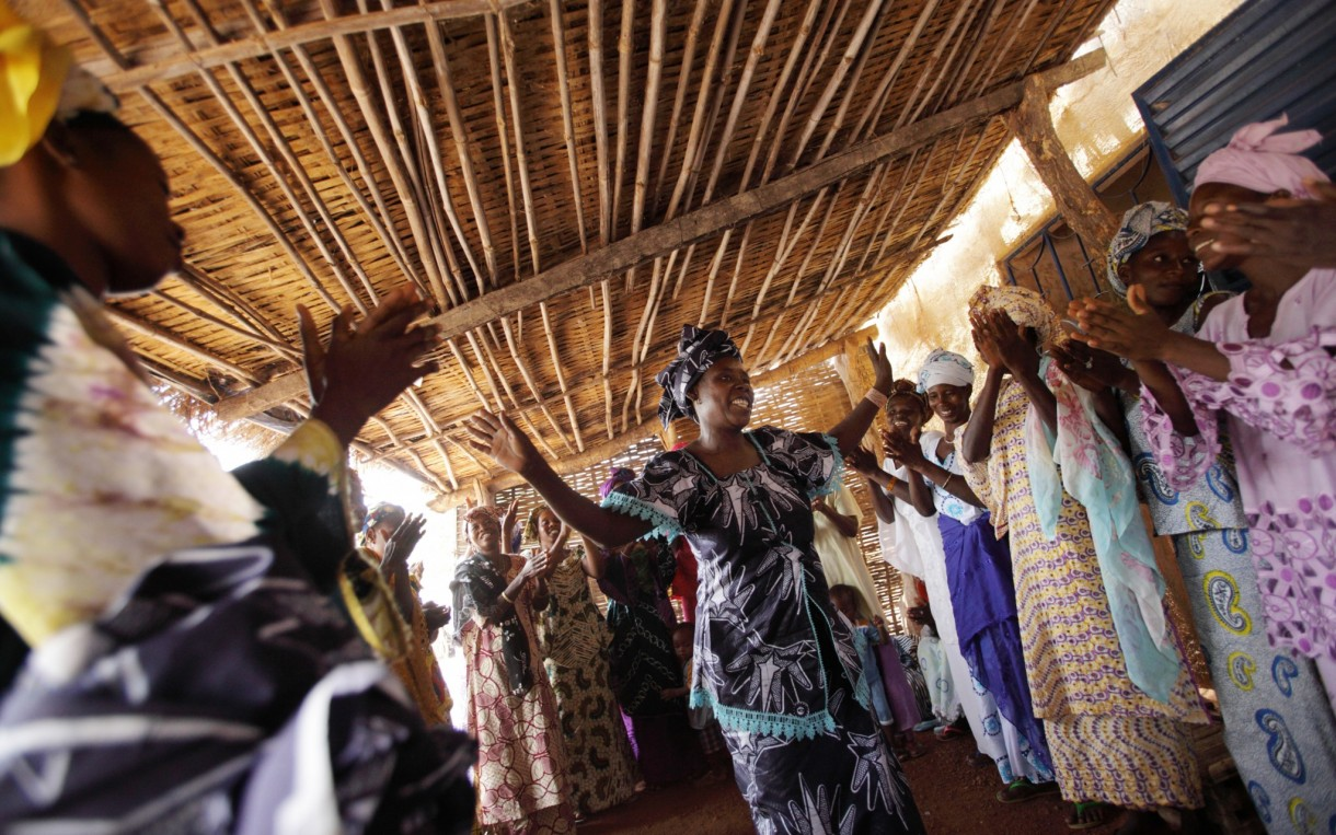 Women from the village of Bandafassi, Senegal celebrate following a Saving for Change meeting. Aminata Barry (center) used group support to create an embroidery business. Photo: Rebecca Blackwell / Oxfam America
