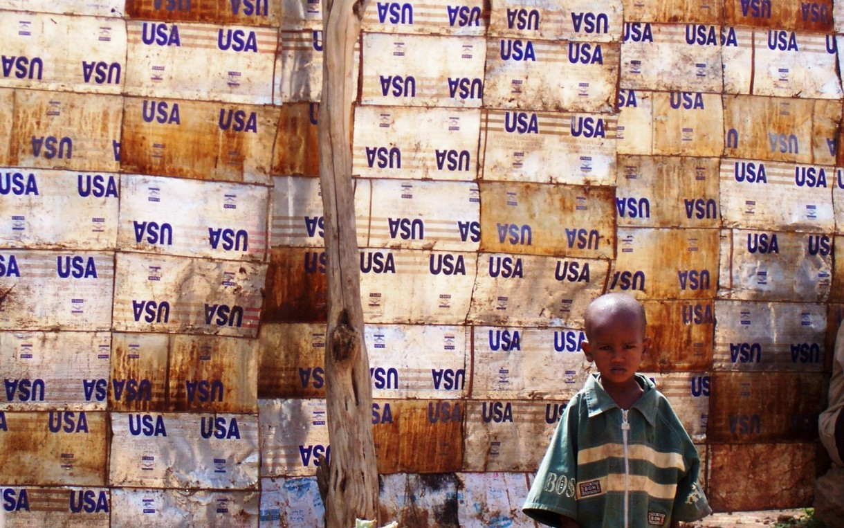 USA Wall, Dire Dawa: Child leaning against wall made of USAID food aid containers in the flood-destroyed area of Bahere Tsege in Dire Dawa. Photo: Liz Lucas/Oxfam America