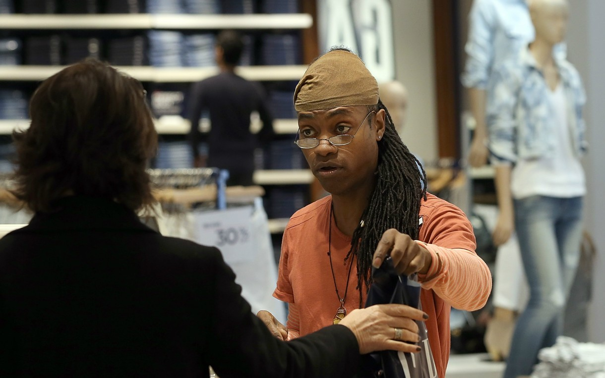Gap employee Ni'Jean Gibson helps a customer in February 2014 in San Francisco. Gap Inc. announced that it will raise its hourly minimum wage for US employees to $9 in June 2014 and to $10 by June 2015. Photo: Justin Sullivan / Getty Images