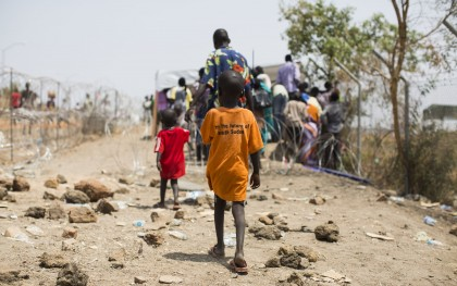 "A young boy trails behind his father and brother as they walk through a ""Protection of Civilians"" site established at the United Nations in Juba. Photo: Mackenzie Knowles Coursin / Oxfam"