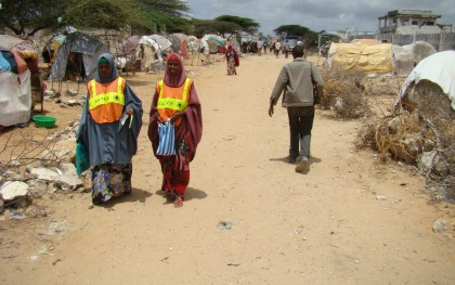 Two community outreach workers walk through the Badbaado Camp for internally-displaced Somalis, located outside of Mogadishu in 2011. They are looking for malnourished children in the camp, referring them to the Community-based Therapeutic Care Center in the camp for treatment and following up with current patients. SAACID (Somali, meaning 'to help'), an indigenous non-profit organization founded and directed by Somali women, admits thousands of malnourished children every month in 16 care centers across Mogadishu. (See more about their work at saacid.org) Although important local programs like these exist, most Somalis are dependent families abroad for financial support. Photo: Geno Teofino / Oxfam