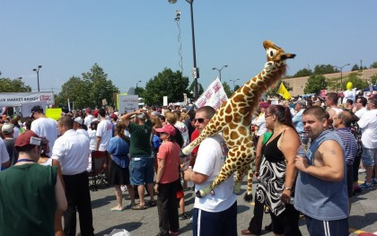 "Grocery workers and consumers rally to ""save Market Basket"" in their Tewskbury, Mass. store parking lot.  The giraffe symbolizes the courage of the workers to ""stick their necks out."" Photo: Minor Sinclair/Oxfam America"