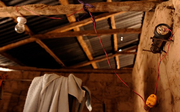 A battery-powered flashlight is rigged to provide electricity to a single lightbulb in a house in the village of Janack in Gambia's Western Region, Monday, May 14, 2007. Photo: Oxfam America/Rebecca Blackwell